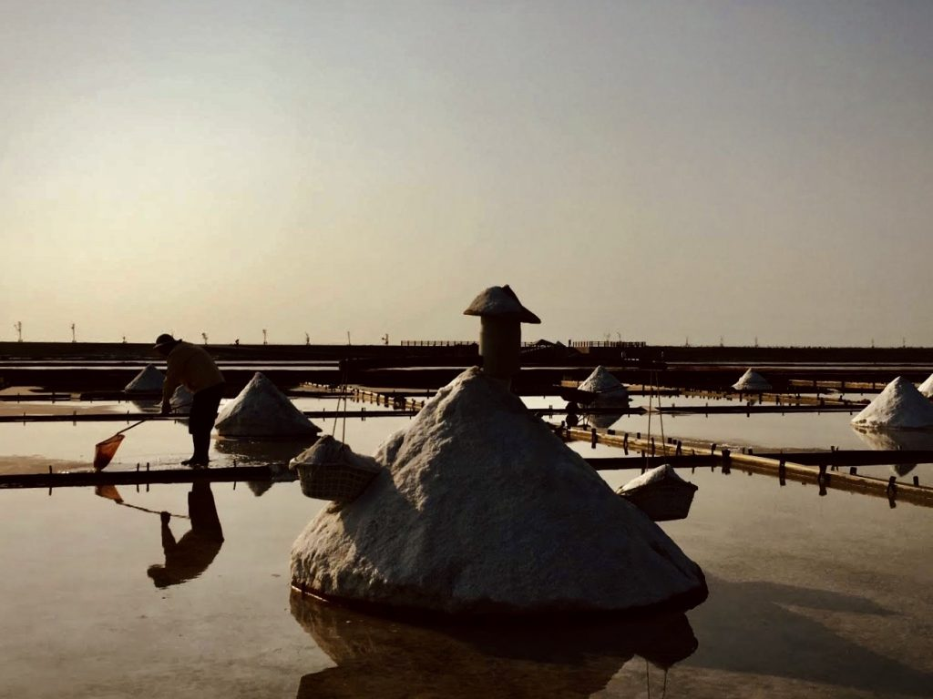 Man raking the salt field at sunset at Jingzijiao Wapan Salt Fields in Tainan