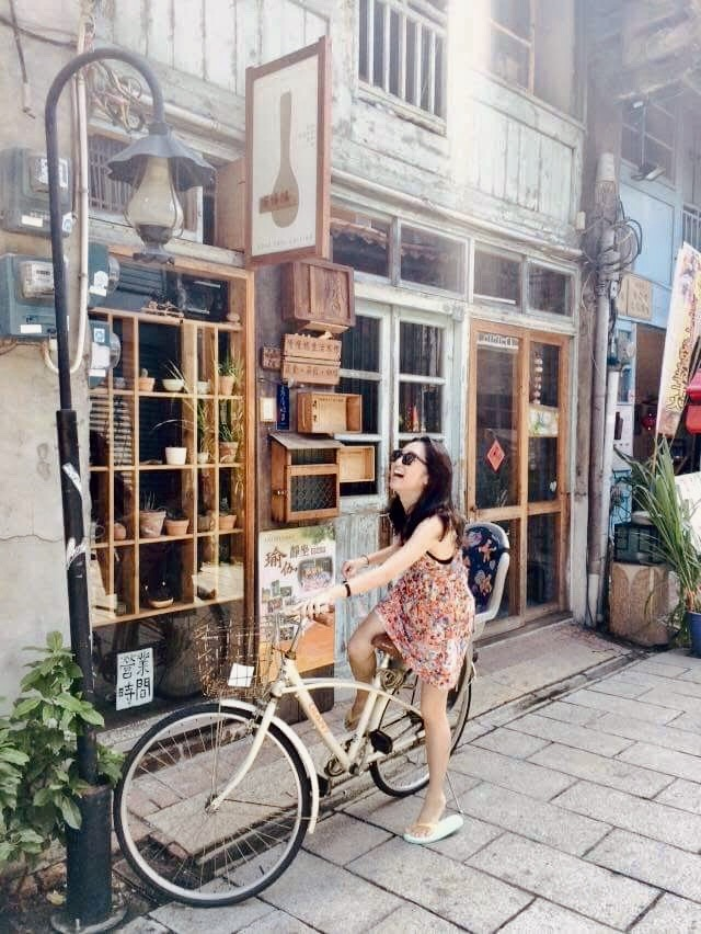 Girl posing with a bicycle outside craft shops on Shennong Street in Tainan