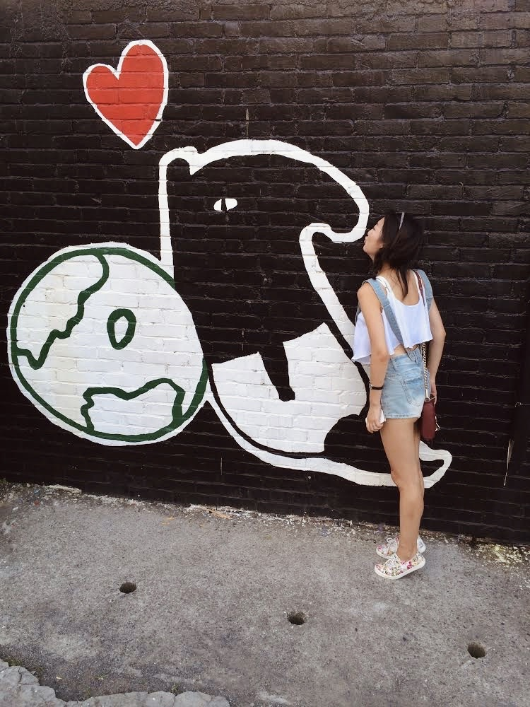 Girl kissing the wall mural of a Malayan tapir by Taiwanese artist Cherng at Shanhua Hu Jia painted village in Tainan