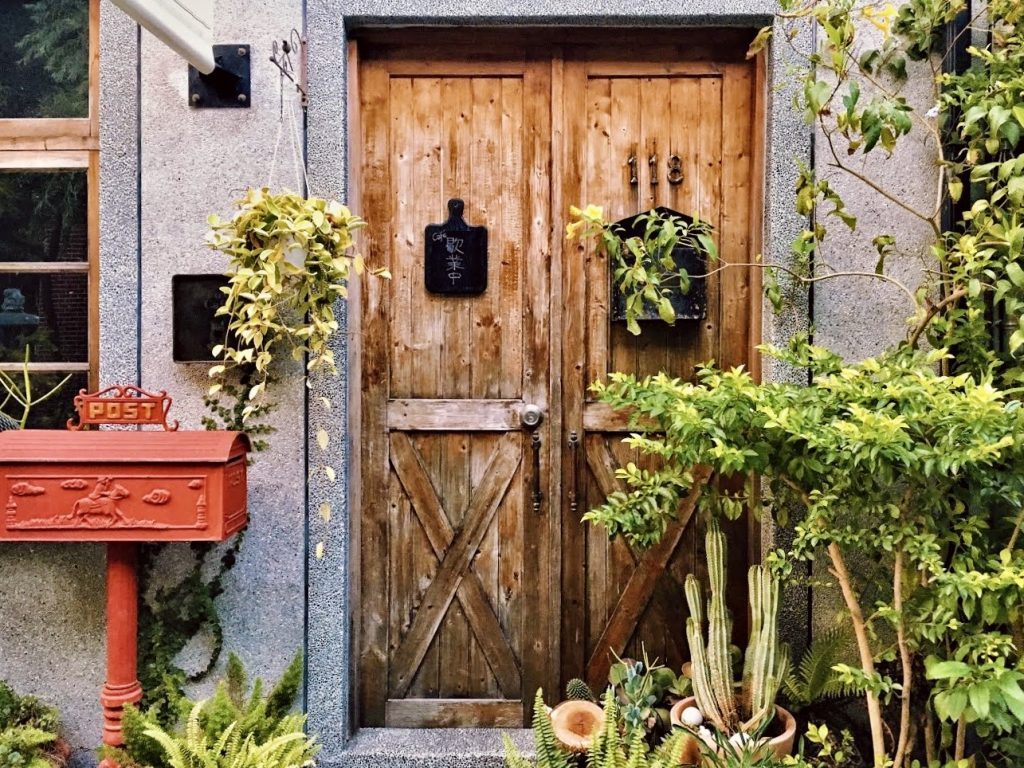A wooden door decorated with shrubs and a bright red mailbox inside Tainan's Duiyuemen