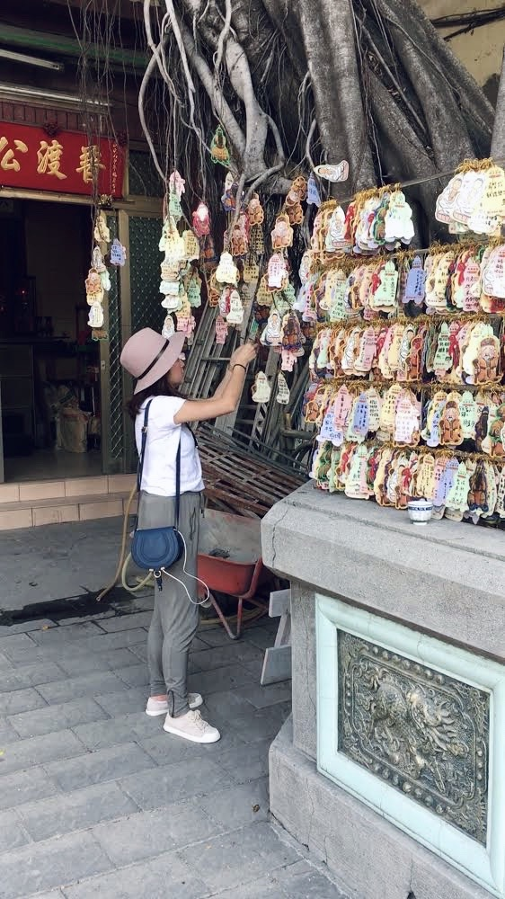 A girl tying her prayer card to a tree at Puji Temple in Tainan