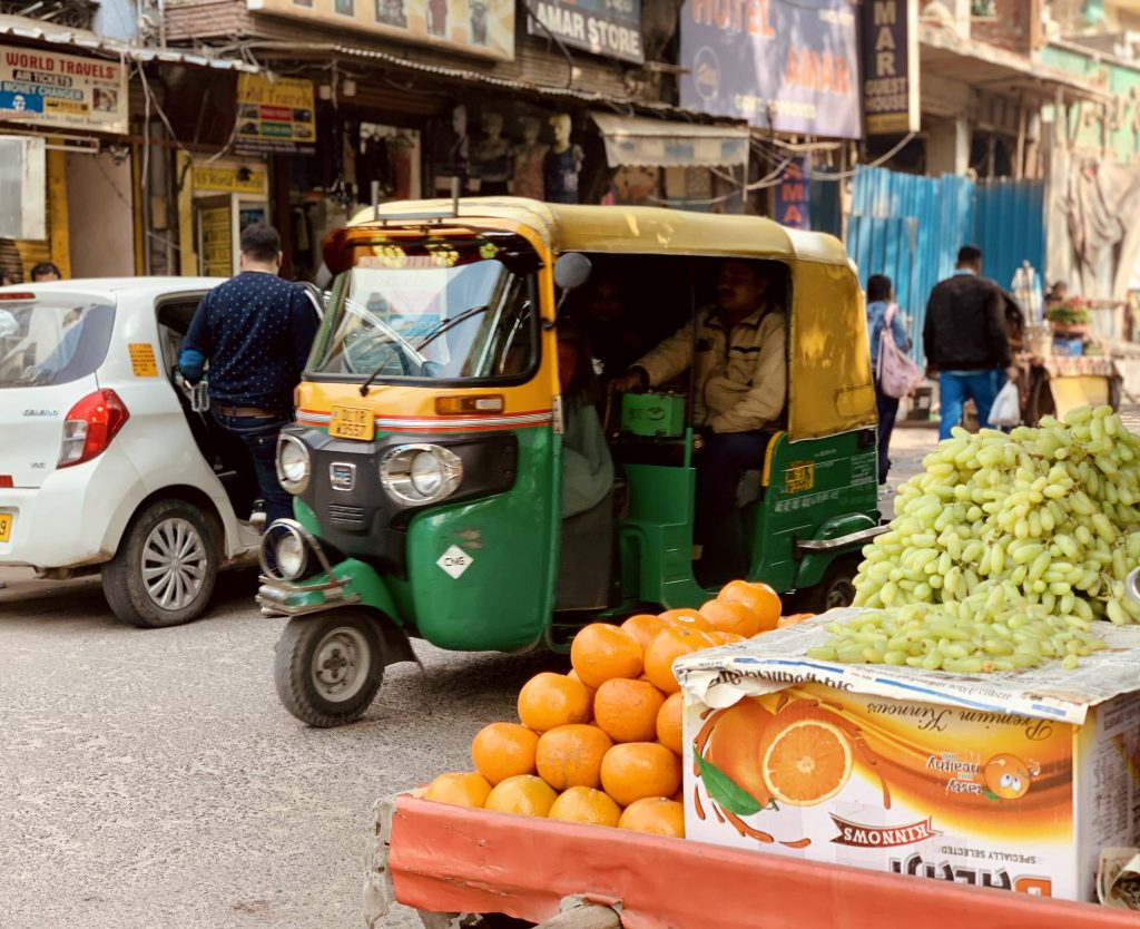 An auto rickshaw passing through the narrow street in Delhi
