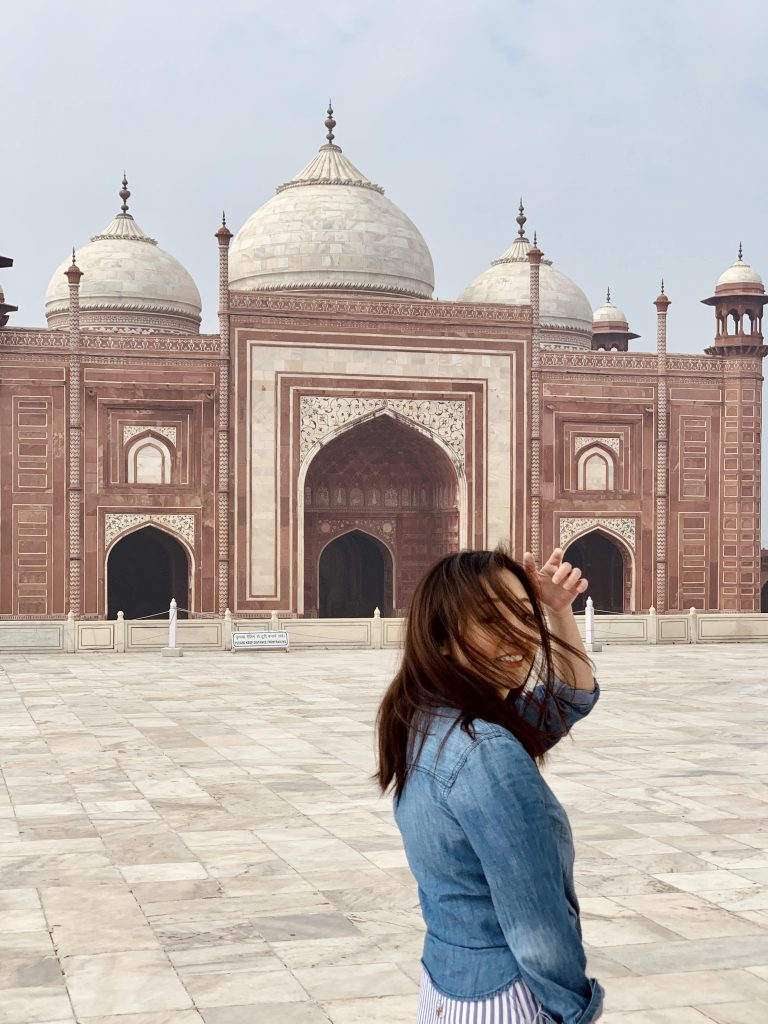 posing in front one of the red sandstone gates at the Taj Mahal