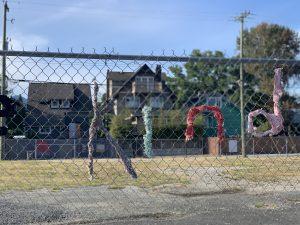 yarn bombing fence art with 'kind' written